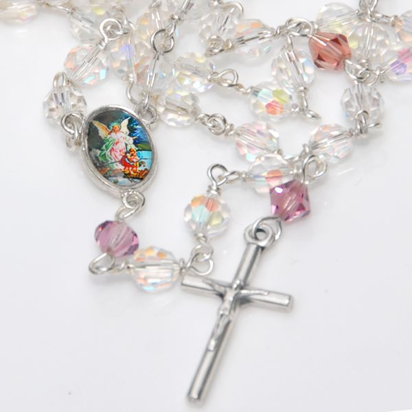 Guardian Angel Christening Rosary - A classically beautiful birthstone crystal Christening rosary.  Aves of lustrous 6mm sparkling faceted clear Swarovski crystal and Paters of 6mm crystal bicones in Baby's birthstone colour. The crucifix is an elegant slim silver tone pewter design measuring 29mm by 14mm.