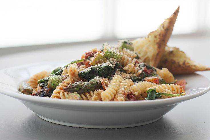 Fusilli Pasta with Delta Asparagus with sun dried tomatoes, spinach, parmesan in tomato garlic basil sauce served with  garlic breadGarlic Bread