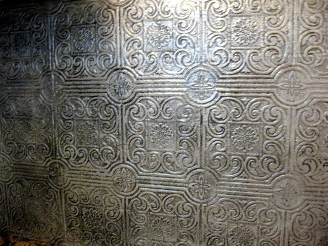 DIY Faux Antique Tin Tile Backsplash. Textured wallpaper painted silver, then she went over it with black glaze to antique it. Maybe copper or gold would work