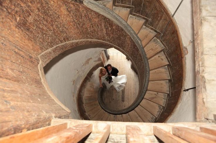Wedding image down ancient spiral staircase from above.