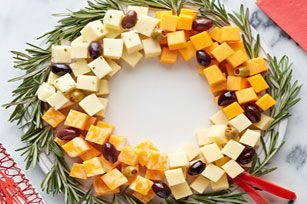 Easy Cheese Wreath. A washable plastic bow would be easier than cutting up a red pepper, and I don't like olives, so I would substitute red grapes, or possibly craisins (dried, sweetened cranberries), or dried cherries for colour. And I could put a clear glass plate ON TOP of a pile of greenery, then I could use whatever greenery I can find, without worrying about whether it's edible, or clean, or arranged in a perfect circle.