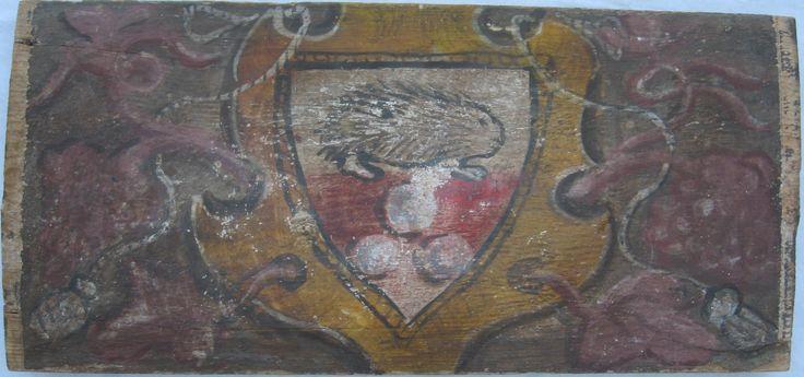 • TAVOLA VIII ter cm 42,8 x 20 x 2,7 BLASONE CON ISTRICE Il retro del legno è integro e solido, come appena sagomato, con la pelosità e le scaglie sollevate dall'ascia del carpentiere, e non è visibile alcun foro di tarlo; per contro, il film pittorico appare fragile con abrasioni, diseguaglianze e affossamenti del legno su cui è applicato il colore. Blasone a scudo appuntato, con istrice passante verso destra su una banda rossa e tre palle disposte a piramide, fondo bianco e cornice…