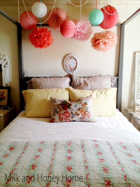 I love the mix of vintage florals with solids and the pom poms overhead. This would be lovely transferred to a crib. #carouseldesigns #babygirl