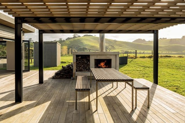 To the rear of the property is the large dining deck. The pergola offers shade from the afternoon sun, while the open fireplace extends the usage of the space to year round.