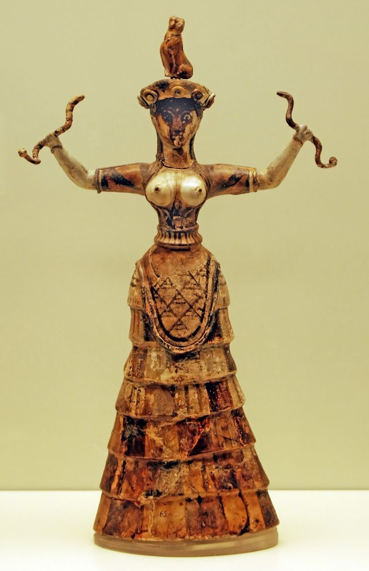 """MINOAN: Snake Goddess, from the palace at Knossos. c. 1600 BCE. Faience, appx. 13 1/2 """" H. Archeological Museum, Herakleion.  Aside from images of bulls, the only obvious deity we have from ancient Crete is the so-called Snake Goddess, perhaps an Earth Goddess who is holding two snakes in her outstretched hands - she is shown with aflounced skirt, and open bodice (evidently standard among Minoan women), and a dove perched on her head which signifies her being divine."""