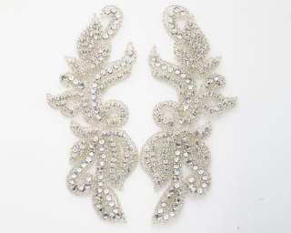 """Beautiful rhinestone applique in a versatile design. Flatback and pointed-back stones give this applique lots of dimension. Cut it up or use it consecutively. Great for neckline, sash, headband. Available as left, right, or matching pair. The cost for a pair is two times the base price.    Size: single piece measures 2.25""""W x 7""""L"""