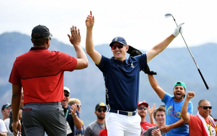 Justin Rose (right) of Great Britain celebrates with Jhonattan Vegas of…