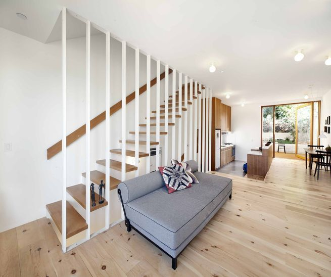 """The first floor contains the living room and kitchen, which opens out onto a petite back garden and anavocado tree. The kitchen is slightly sunken and has a polished concrete floor, which subtly demarcates it from the rest of the space.Materials in the kitchen set the home's materialpalette, withvertical Douglas fir cabinets and the same 3"""" x 6"""" subway tiles that appear in the bathroomfor the backsplash. The Fisher & Paykel dishwasher is hidden inside the island: """"I wanted the ..."""