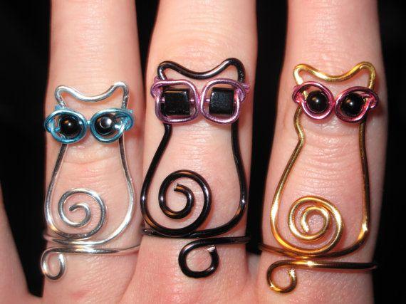 ESTE LISTADO ESTÁ PARA UN ANILLO SÓLO! SELECCIONAR SUS COLORES Y FORMA DE MATICES EN LA COMPROBACIÓN!  Estos anillos están hechos a mano y alambre envuelto en un anillo de gato adorable. Envuelto en su color de elección de alambre, luego completa usando su elección de gafas de sol. Son ajustables para adaptarse a cualquier tamaño. ¡ Son tan adorable y tan divertido para todos los gato amantes por ahí!  CONVO SI DESEA UN ANILLO DE EXACTO TAMAÑO PARA AJUSTARLO DE SALIDA!  SELECCIONAR EL COLOR…