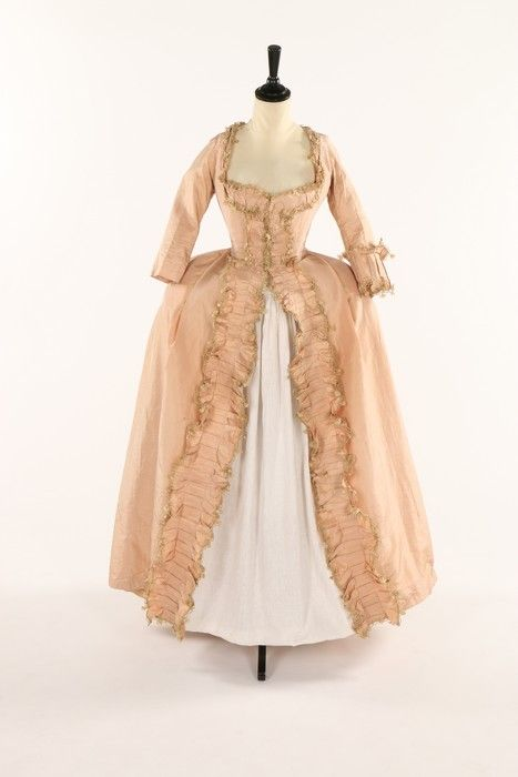 Robe à la francaise, 1770s. Pink-peach silk taffeta, fabric trimming and golden fly fringe.