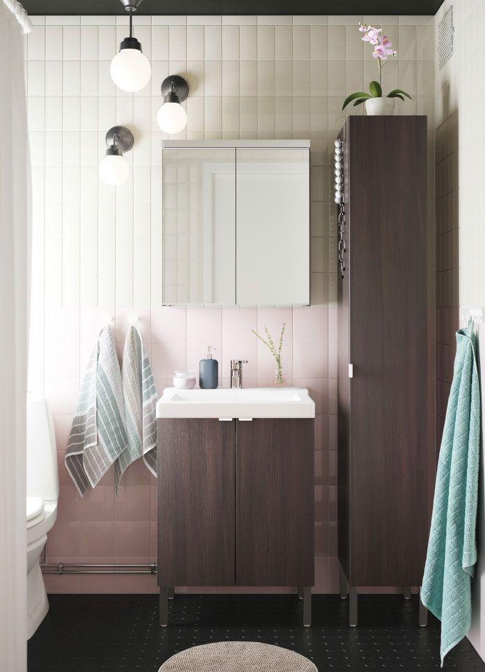 Lite, hvitt bad med mørk brunt høyskap, et speilskap og et mørk brunt servantskap med to dører.