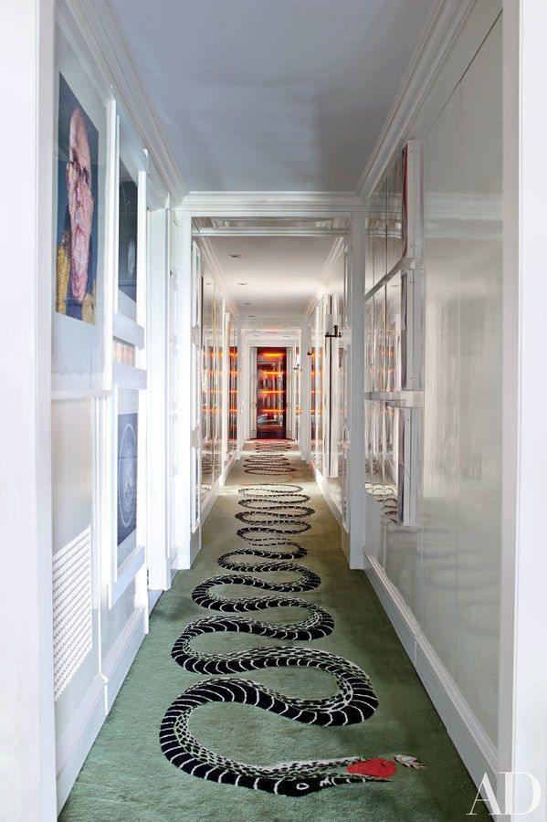 A light installation glows in a hall carpeted with a striking snake design | archdigest.com