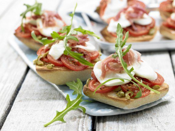 This easily prepared sandwich is piled with green olives, tomatoes, serrano ham, and mozzarella cheese topped off with peppery arugula. | Eat Smarter