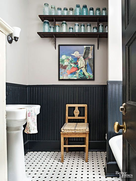 A little bit country, a little bit cottage, this bathroom pays tribute to long-ago lavatories in modern ways. References to farm life include a rural rendering, a canning-jar collection, and a primitive coverlet folded on an antique chair. The tiled floors and black painted wainscoting give a nod to cottage style in high-impact fashion./