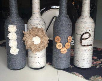 Bottiglia di vino di amore a mano avvolto in spago iuta e filato bianco con fiori nastri pulsanti ed archi oh mia bella usare ad un matrimonio shabby chic di paese e per la casa come un vaso o lasciare così comè.  Forme di bottiglia di vino, colore e dimensioni variano come ogni ordine è fatto a mano due bottiglie non saranno esattamente uguali.  Per visualizzare ulteriori PeavyPieces splendidi oggetti artigianali per favore clicca qui: https://www.etsy.com/shop/PeavyPieces  Per visualizzare…