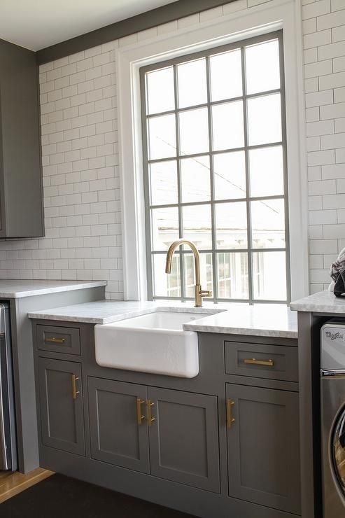 Charcoal gray laundry room features charcoal gray shaker cabinets adorned with long brass pulls is topped with carrera marble fitted with a farmhouse sink and a brass gooseneck faucet.