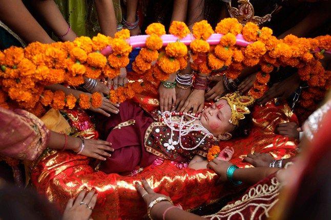 A child dressed as Krishna is cradled during the Janmashtami festival, acelebration of the Hindu lord. #Hindu #Festival #India