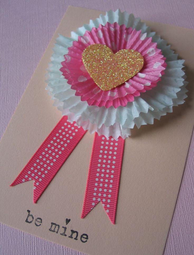 Materials:    Cupcake liners in assorted colors and sizes  Pinking shears (optional)  Double-sided tape or quick-setting craft glue  Heart punch or template  Fine glitter  Ribbon  Pin backs or small, flat magnets  Plain cardstock  Ruler and craft knife (or a paper trimmer)   Valentine stamps  Ink