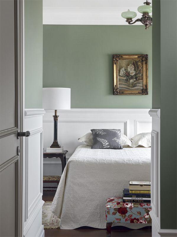 Peças douradas ganham destaque junto ao verde acolhedor. Sobre a cama, almofada com folhagens da Conceito Firma Casa. Nas paredes, Verde Pinheiro (Suvinil).