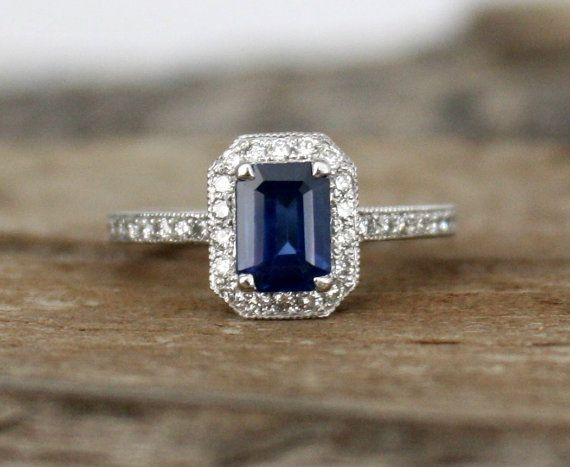 Hand milgrained 14K white gold diamond halo ring featuring a natural emerald cut cornflower blue sapphire measuring 6.8 x 5 mm and weighing 1.17 cts.