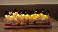 Traktatie voor mijn dochters 5e verjaardag. Cupcakejes bakken, dun laagje rolfondant erover. Mandarijntje in wit crêpepapier inpakken. Elektrisch waxinelichtje op tapas prikker plakken (secondelijm, 1 dag van te voren). Van dik zwart papier hoedje uitknippen en op lichtje plakken. Prikker door mandarijn heen steken in cake. Met permanent marker stippen zetten