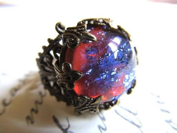 Large and spectacular dragons breath opal jewel is a ruby red with shifting flashes of cool blue and purple with every move. Set with ornate prongs in a crown setting and a filigree band. Perfect for Cosplay or everyday. Giving it as a gift? Dont know what size? This ring is versatile