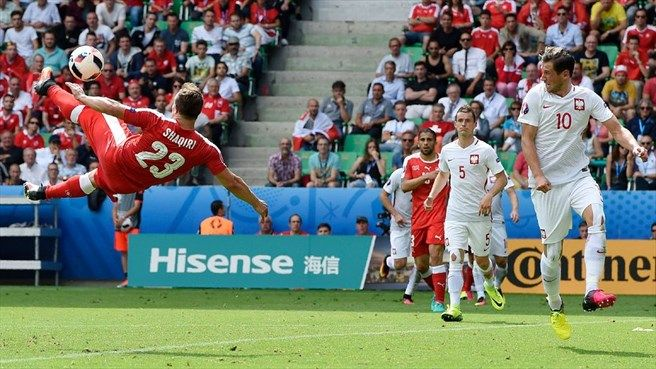 Xherdan Shaqiri (L) of Switzerland scores their first goal during their UEFA EURO 2016 Round of 16 match against Poland