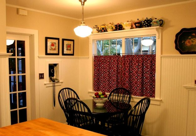 High, crisp, white wainscoting and buttery yellow walls provide a neutral background for a dramatic splash of red and black. Shelves above the windows and a recessed area for a telephone create added interest.