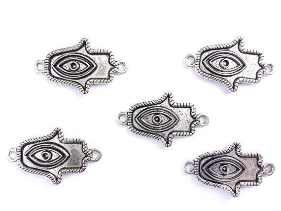 Conectores de mano de Fátima y ojo turco. Color plata, ideal para hacer pulseras. Hazlo tú mismo. Conector mal de ojo. Material de joyería. Amuleto. Medida: -ancho 3.5 cm -alto 2 cm Se vende en lote de 5 unidades. Aleación de metales (no contiene zinc, plomo ni níquel) Puedes ver trabajos acabados, en mi otra tienda https://www.etsy.com/es/shop/xannachip Si quieres varios articulos escribeme y ajustamos el precio de envio Hand and Fatima eye connectors. Silver color...