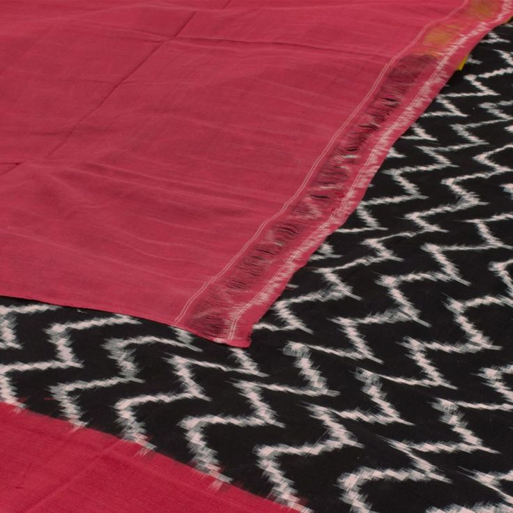 """The """"#Black"""" #handwoven #Ikat #Cotton #Sari from Karghaa is woven with white waves all over the body that is set off by a pink and yellow border on either side. An attractive pink pallu adorn the sari. The yellow blouse completes the sari."""