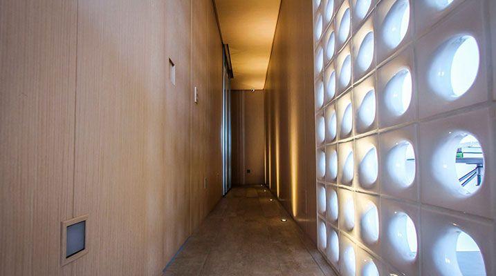 Corredor dos quartos com iluminação indireta , cobogó em esmalte branco e  painéis de madeira freijó linheiro com puxadores esculpidos nas portas - Bruno Moraes Arquitetura