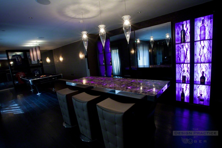Bespoke purple amethyst bar with closed partitions showing display columns and the pool/games area beyond with trophy cabinet