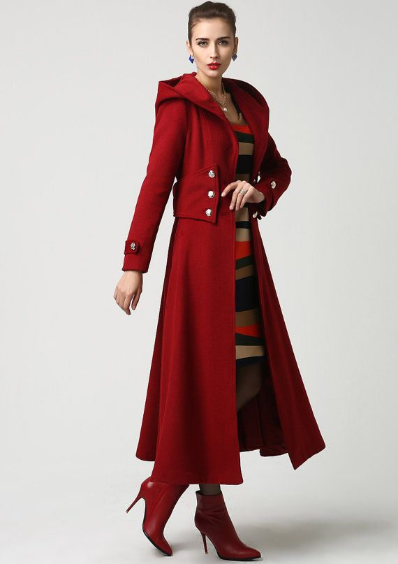 Every woman needs a classic red coat in her wardrobe, and this hooded version is a stunner. The oversized silver button accents with form fitting bodice leading into a long flowing skirt, making this coat so stylish and feminine. One of the nicest details is the wide cumberband style waistband, really accenting the waist. This coat has a style reminiscent of coats from the 1940s.    DETAILS:  * soft wool fabric,50% wool blend * polyester lining * warm hood * side hip pockets * button tabs…