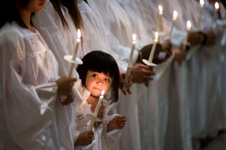 In this Saturday, April 4, 2015 photo, Vietnamese-American Jillian Nguyen, 3, stands with others during their baptism into the Catholic faith, at Saint Helena Catholic Church in Philadelphia.