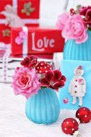 Weihnachtliche Dekoration in Blau & Rot mit Blüten in Vase, Christbaumkugeln & Geschenken