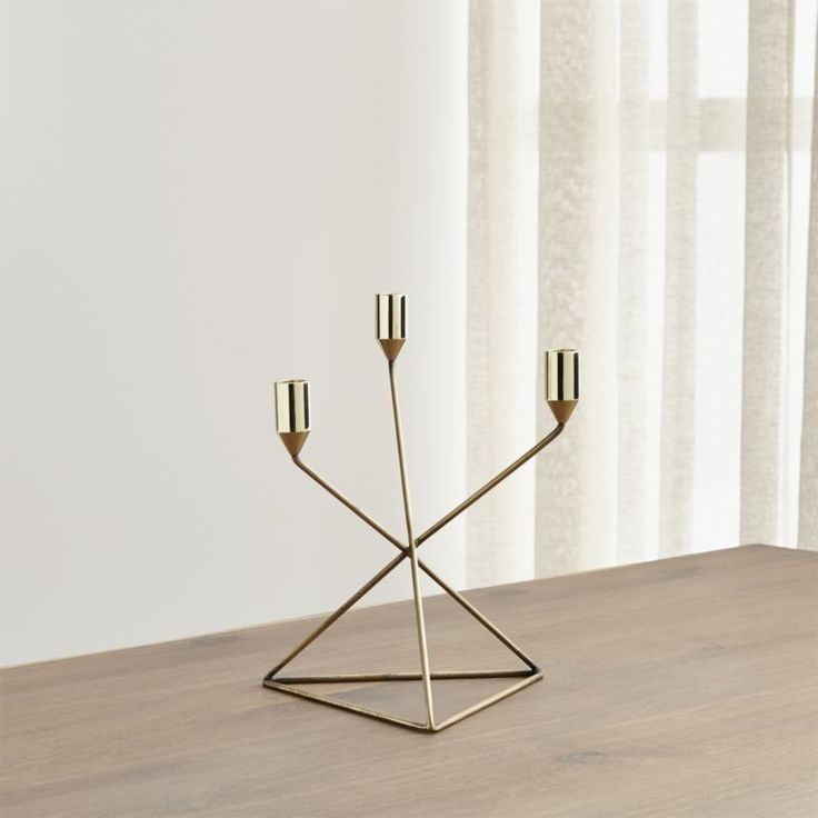 In a new angle on candlelight, our geometric modern candle holders with gleaming brass-plated finish displays three tapers at staggered heights for a striking centerpiece.