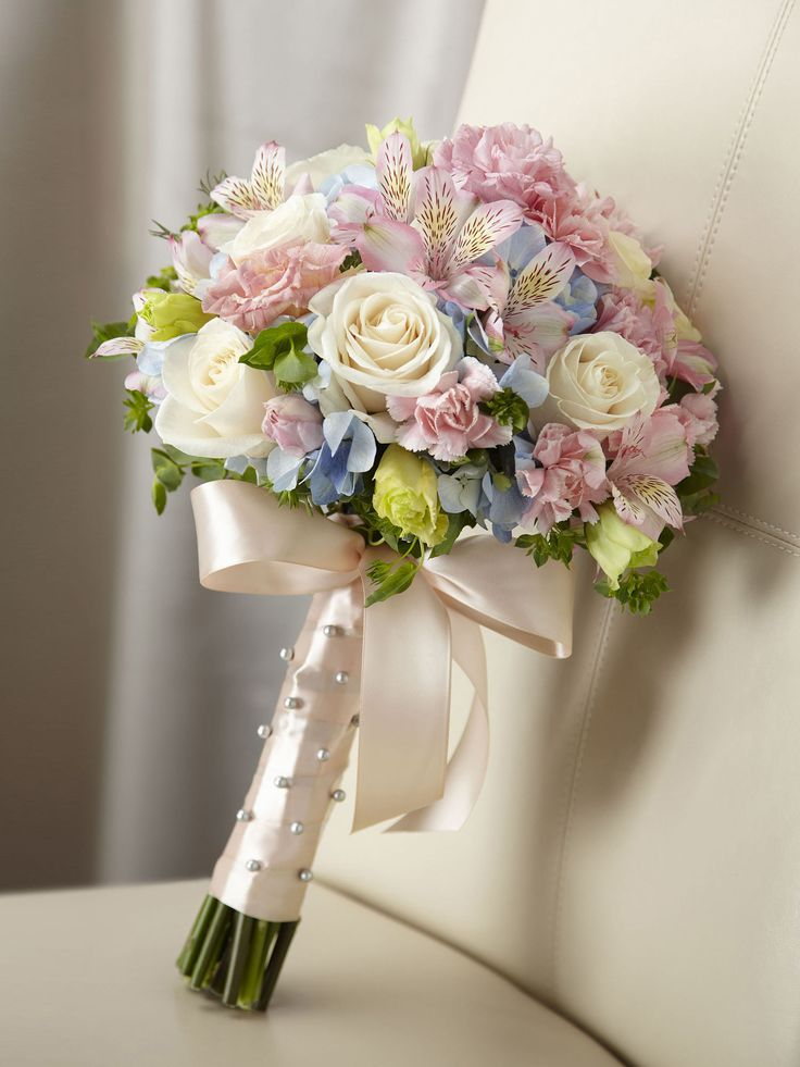 Blooming with sweet sentiments and endearing charm to get you to look your bridal best on your wedding day. Stunning cream roses, pink mini carnations, pink alstroemeria, pink double lisianthus, blue hydrangea and bupleurum are brought together to create a picture-perfect bouquet.