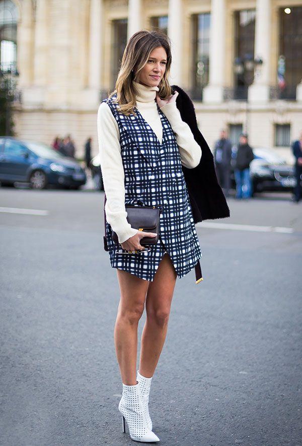 Street style look Helena Bordon com colete xadrez, bota branca e blusa com gola turtleneck manga longa.