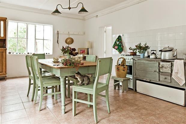 Cocina de una casa en Chubut, Argentina, con juego de comedor pintado en verde claro, piso de cerámica en color tierra y banco rústico de madera.