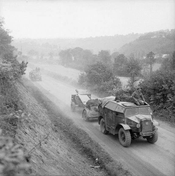 British 25-pdrs and 'Quad' tractors advancing towards Vire, 2 August 1944.