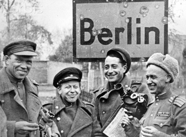 End of the war in Berlin 1945 - Soviet soldiers holding camera equipment and a map are photographed in front of a city sign in Berlin, Germany. Photo: Berliner Verlag / Archive - NO WIRE SERVICE