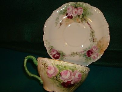 A BEAUTIFULLY HANDPAINTED Cup & Saucer with the VINTAGE JP/L Mark on both pieces. Great Pink and Red roses with Green Trimmed Handle and Gold Gilding on Rim of both pieces. Saucer is 5 1/2 and top of