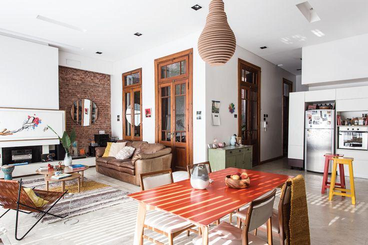 El living-comedor integrado a la cocina. Mesas bajas danesas de 1m de diámetro ($7.200) y de 0,60m de diámetro ($5.400, todo de Broca), ambas hechas en madera de petiribí. Sobre la mesa, florero de vidrio ($189, Falabella).  /Daniel Karp