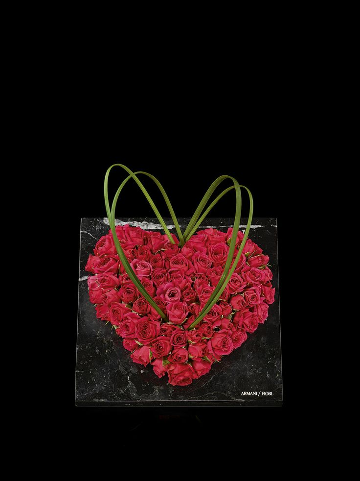 a bed of red roses shaped like a heart on black marble tile #Armani/Fiori