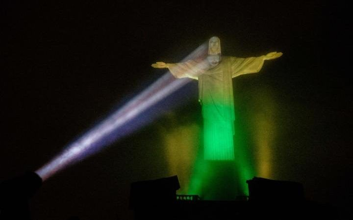 The statue of Christ the Redeemer is illuminated in Brazilian flag colors, including a projected face designed by Brazil based Italian-French lighting artist Gaspare Di Caro, to celebrate 100 days until the start of the Olympic Games Rio 2016
