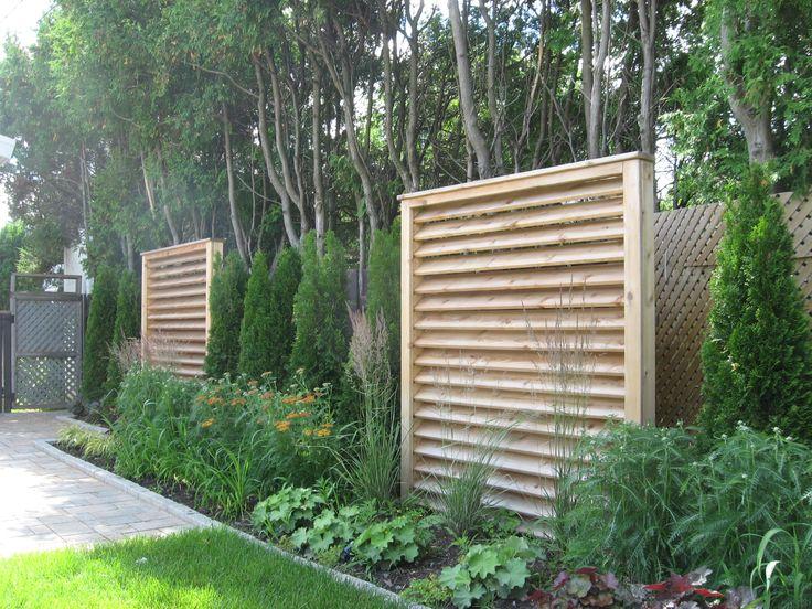 Écrans de cèdre modernes mis en place dans une cours pour la rendre plus intime. Haie de cèdre et jardin urbain. Végétation. - Wood screens. bushes and shrubs. Urban garden.