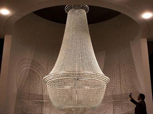 """14,000 unused repurposed tampons are spun together with wire and thread to form a stunning chandelier entitled Bride. The 5m (16' 5"""") tall chandelier is part of an exhibit by Portuguese artist Joana Vasconcelos on display at the Belem Cultural Center in Lisbon until May 18, 2010."""