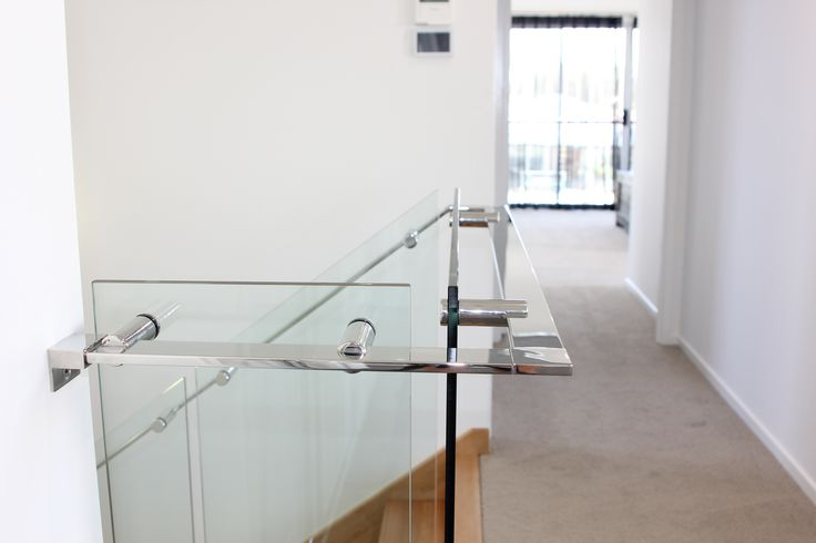 Frameless glass staircase balustrade with custom made stainless steel handrails and standoffs.