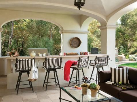 A Mediterranean loggia featuring white arches offers an escape from sunny days with an outdoor bar area and striped padded stools, stone tiled floor, and brown decor.