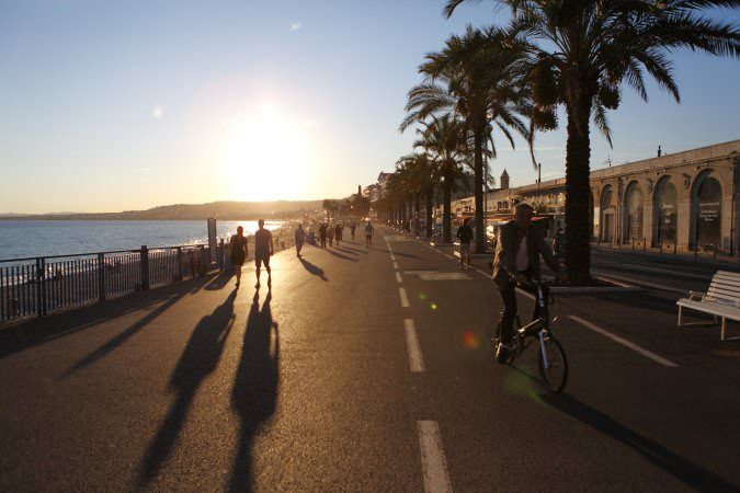 People on palm lined Promenade des Anglais, Nice, France